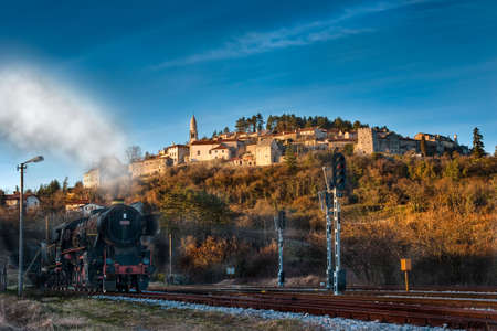 Old locomotive passing a old sunlite vilage on the hill Stock Photo