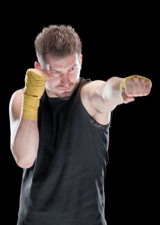 Young man in defensive boxing pose isolated on black
