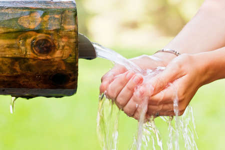 Woman hands holding water coming from a spring.