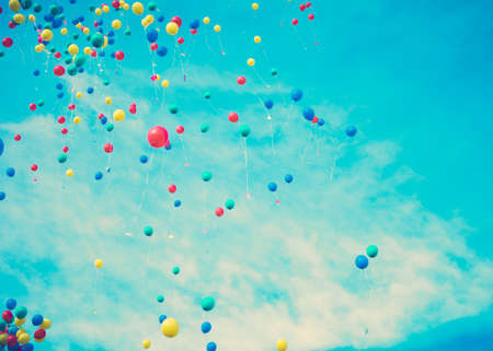 blue grunge background: Colorful helium balloons in flight