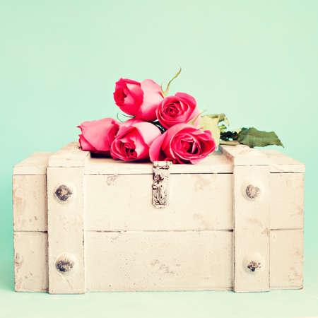 ビンテージ木製胸の上の赤いバラ
