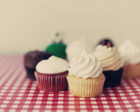 Various cupcakes over a checkered tablecloth photo