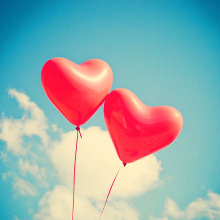peace and love: Two red heart-shaped balloons