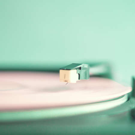 Vintage turntable with pink vinyl record photo