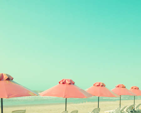 Vintage summer beach with pink umbrellas photo