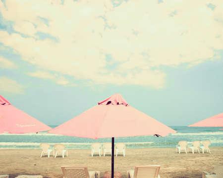 与桃红色伞的葡萄酒夏天海滩