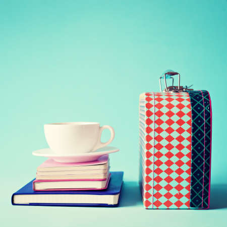 Vintage lunchbox with tea cup and notebooks photo