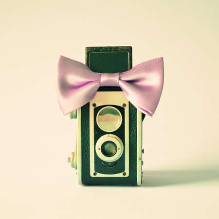 Vintage film camera with purple bow tie photo