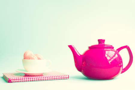 コーヒーのカップと赤のティーポットのマカロン