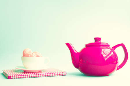 Macaroons in a coffee cup and red teapot Stock Photo