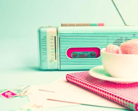 türkis: Rosa Makronen in einer Tasse Kaffee und Vintage-Radio Lizenzfreie Bilder