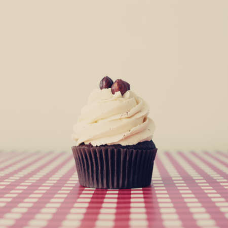 Hazelnut cupcake over white and checkered background photo