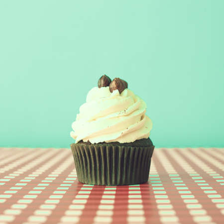 Hazelnut cupcake over turquoise and checkered background photo