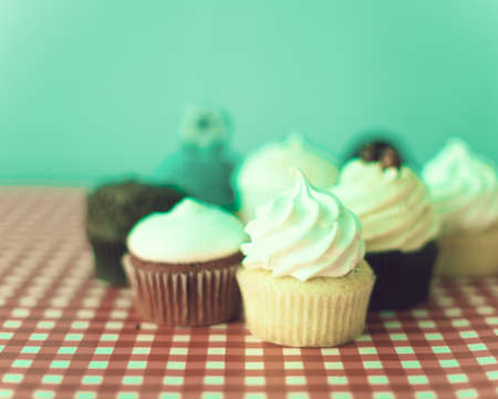 Various cupcakes over turquoise and checkered background photo