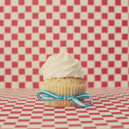 Vanilla cupcake over checkered background photo