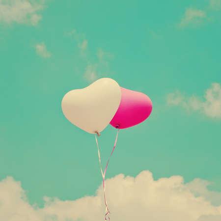 romantic sky: Two heart-shaped balloons