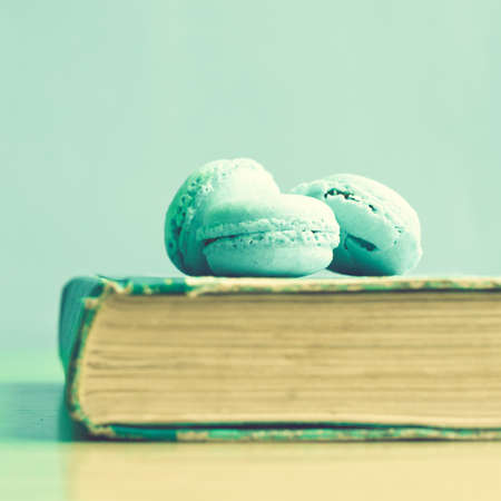 Turquoise macaroons over vintage book photo