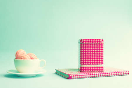 Pink macaroons in a white cup with tea box and vintage book photo