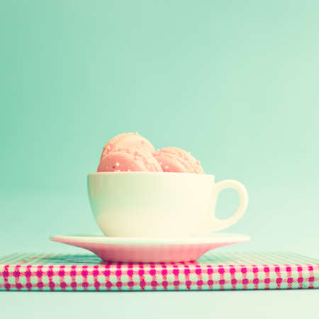 Pink macaroons in a cup over vintage book photo