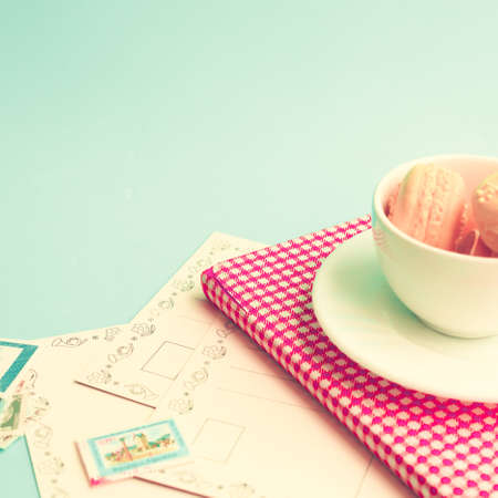Pink macaroons in a white tea cup with vintage book and postcards photo