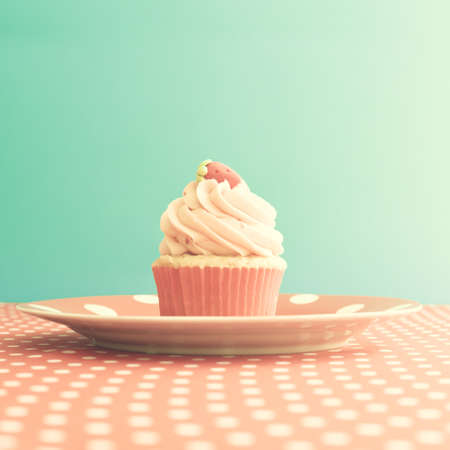 Strawberry cupcake over polka dots photo