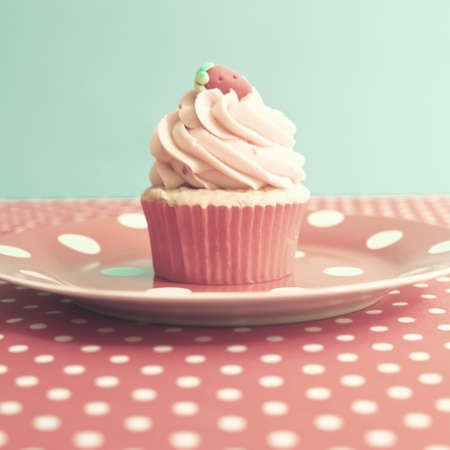 Strawberry cupcake over polka dots photo