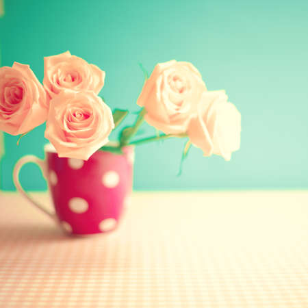 Pink roses in a polka dots vase photo