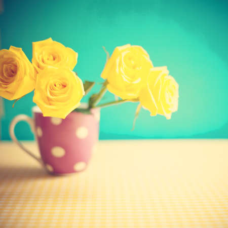 Yellow roses in a polka dots vase photo