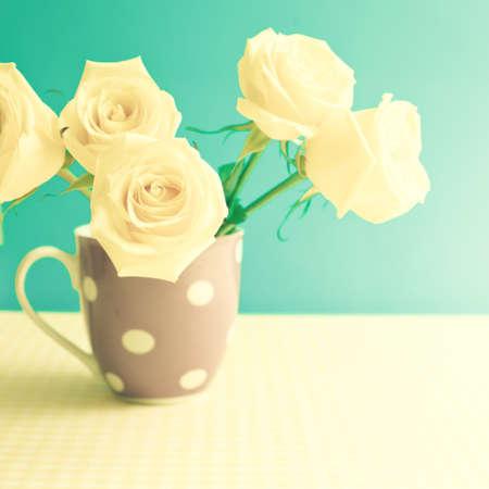 White roses in a polka dots vase Stock Photo