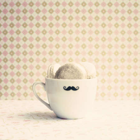 Macaroons in a vintage tea cup with mustache photo