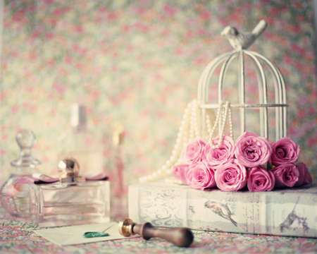 romance: Rosas sobre livro vintage, frascos de perfume e selo de lacre