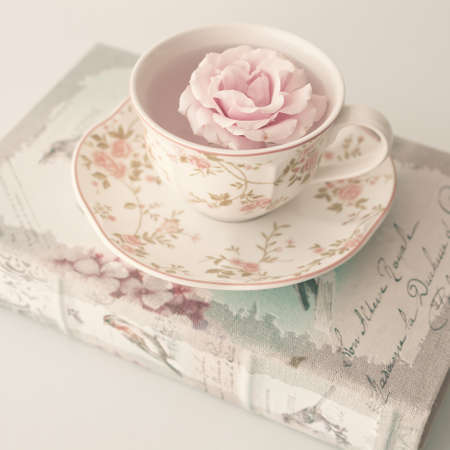 Rose in a vintage tea cup over antique book