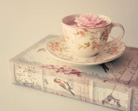 taza de te: Rose en una taza de t� de la vendimia sobre el libro antiguo