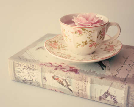 tea filter: Rose in a vintage tea cup over antique book