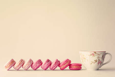 tea and biscuits: Line of macaroons and vintage tea cup Stock Photo