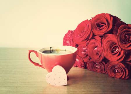 バラの花束赤、コーヒー カップと木製の手描きの心 写真素材