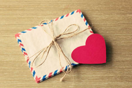old envelope: Vintage mail envelopes and paper heart over wood