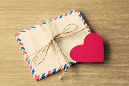 old envelope: Vintage mail envelopes and paper heart over wood