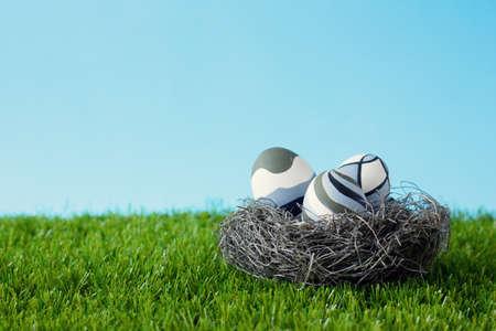 Uitstekende paaseieren in een nest over gras