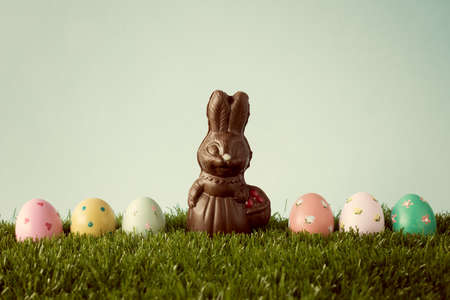 Vintage chocolate easter bunny with easter eggs over grass