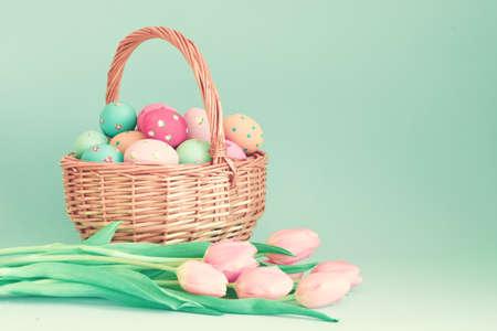 huevo: Huevos de Pascua en una cesta y tulipanes de color rosa Foto de archivo
