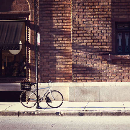 brick building: Vintage bicycle parked in front of a brick building
