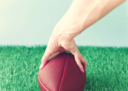 Vintage football over grass being held Stock Photo
