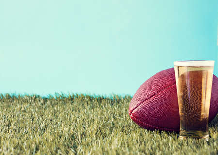 handoff: Vintage football over grass and beer glass