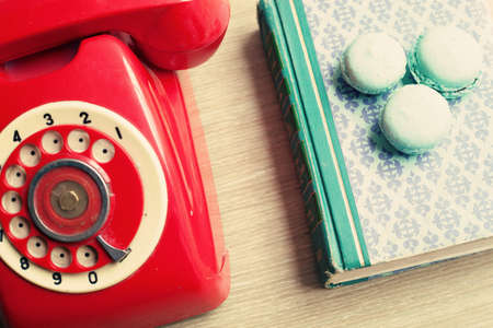 red telephone: Vintage red telephone and macaroons over book