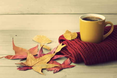 autumn colors: Coffee cup over a red scarf and autumn leafs