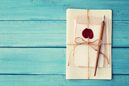 schreiben: Vintage-Papier und Stift über türkisfarbenen Holz