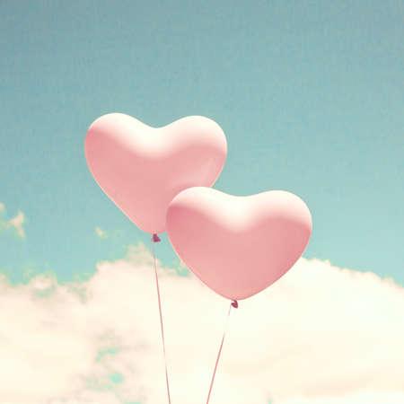 ターコイズ ブルーの空に風船の形をした 2 つのピンクのハート