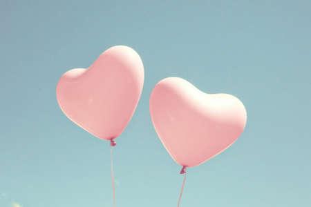 Zwei rosa herzförmige Luftballons in türkisfarbenen Himmel