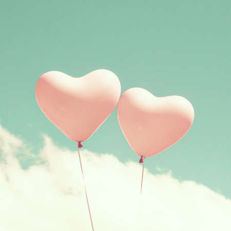 photography: Two pink heart shaped balloons in turquoise sky